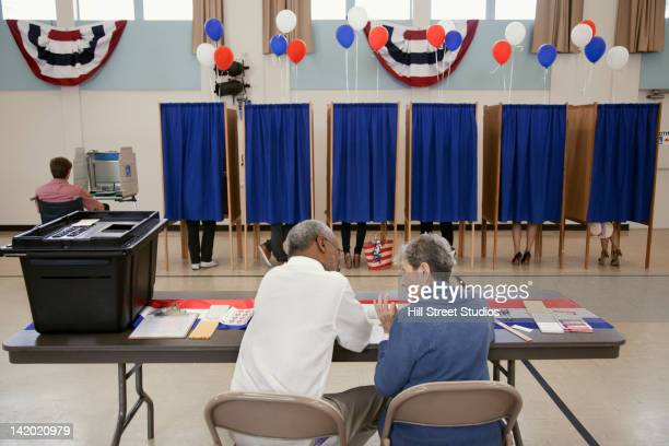 workers sitting at registration desk in polling place - election day stock photos and pictures