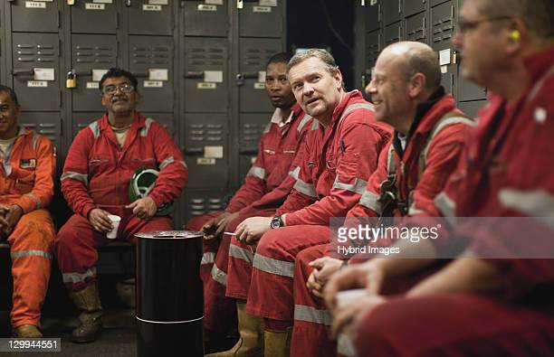 Workers sitting in locker room