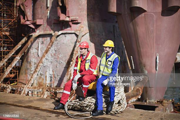 Workers sitting on rope on oil rig