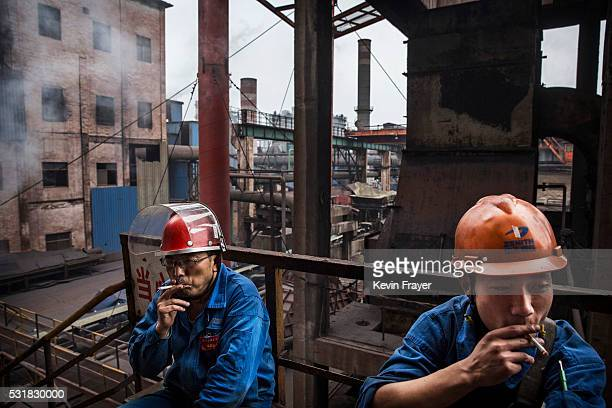 Workers smoke at the end of their shift outside a furnace for molten iron in the production area of the Zhong Tian Steel Group Corporation on May 13,...