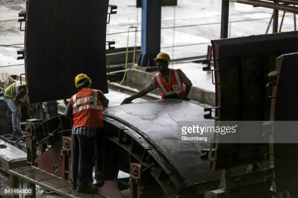 Workers smooth the surface of a precast concrete tunnel segment as it sits in a mold at the Mumbai Metro Rail Corp casting yard in Mumbai India on...