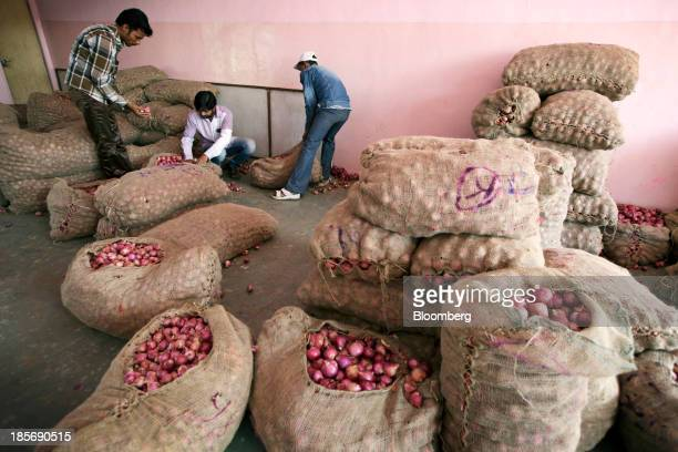 Workers sort bags of onions at a wholesale market in Nashik Maharashtra India on Wednesday Oct 23 2013 Onion prices in India may extend a record...