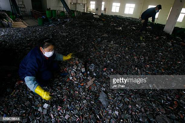 Workers sort batteries in an electronic waste recycling factory in Jingmen Hubei province December 3 2009 VCP