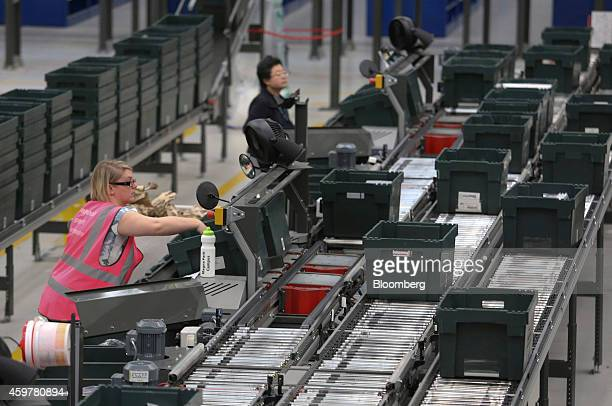 Workers sort customer 'click and collect' orders into crates destined for John Lewis stores at the John Lewis Plc semiautomated distribution centre...