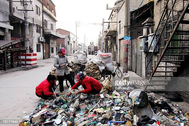 Workers sort garbage on the street in front of their workshop on February 1 2007 at Lianjiao Foshan city Guangdong province of China Following recent...
