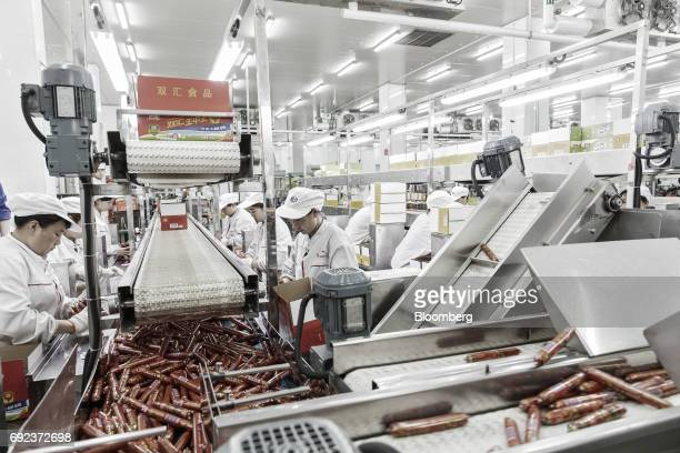 Workers sort packaged sausages on a production line that manufactures Shuanghui branded sausages at a WH Group Ltd facility in Zhengzhou China on...