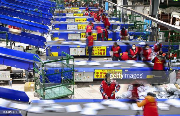 """Workers sort packages after the """"Singles Day"""" shopping festival at a delivery company in Hengyang in China's central Hunan province early on November..."""