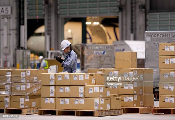 Workers sort packages at the All Nippon Airways Co's cargo hub terminal at Naha Airport in Naha City Okinawa Prefecture Japan on Friday Feb 24 2012...