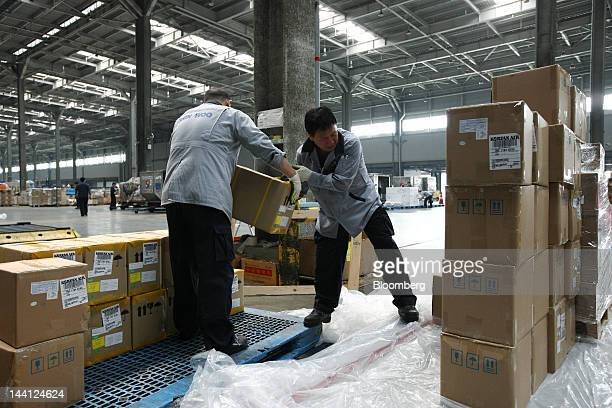 Workers sort packages from Hong Kong at a Korean Air Lines Co cargo terminal at Incheon International Airport in Incheon South Korea on Thursday May...