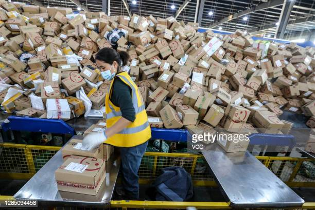 Workers sort parcels at a branch of China Post during 2020 Double 11 Shopping Festival on November 11, 2020 in Huai an, Jiangsu Province of China.