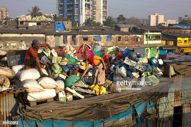 Workers sort plastic for recycling on a rooftop in the Dharavi slum on February 3 2009 in Mumbai India The redevelopment of asia's largest slum the...