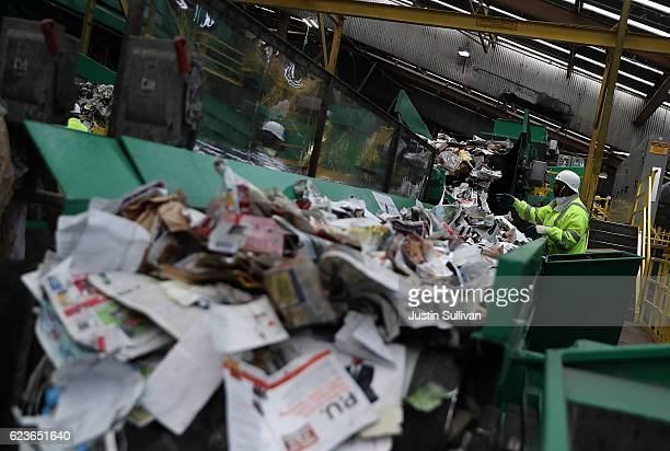 Workers sort recyclable materials as they pass through a sorting machine at Recology's Recylce Central on November 16 2016 in San Francisco...