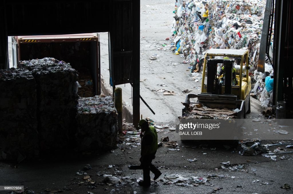 Workers sort recycling material at the Waste Management Material Recovery Facility in Elkridge, Maryland, June 28, 2018. - Some 900 tons of trash are dumped at all hours of the day and night, five days a week, on the conveyor belts at the plant. For months, this major recycling facility for the greater Baltimore-Washington area has been facing a big problem: it has to pay to get rid of huge amounts of paper and plastic it would normally sell to China. But Beijing is no longer buying, claiming the recycled materials are 'contaminated.'