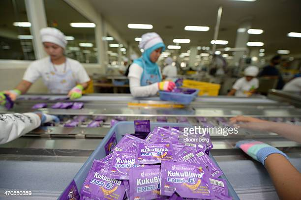 Workers sort sachets of Kuku Bima EnergG energy drink powder along a conveyor at the packaging section of the PT Industri Jamu Dan Farmasi Sido...