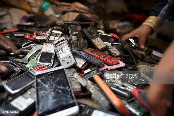 Workers sort through a pile of used mobile phones in New Delhi India on Thursday June 18 2015 The rupee climbed 08 percent in the five days ended...