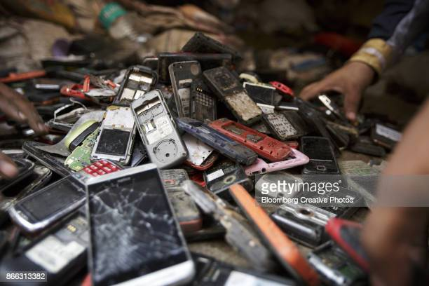 Workers sort through a pile of used mobile phones in New Delhi, India