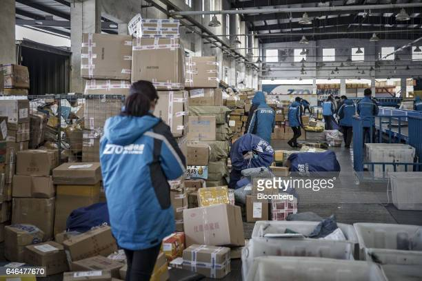 Workers sort through packages and boxes at a ZTO Express Inc sorting facility in Shanghai China on Friday Feb 10 2017 Package delivery...