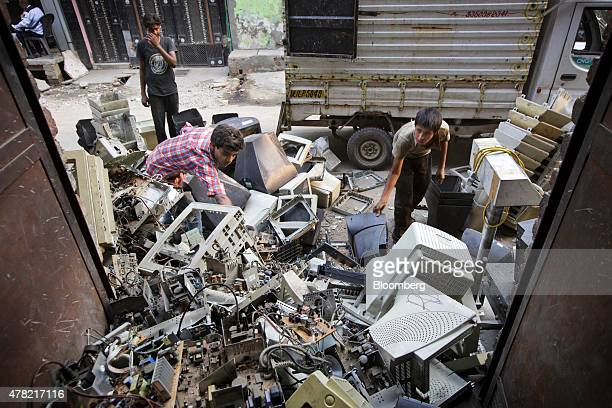 Workers sort through used computers and other electronic waste at a workshop in New Delhi India on Thursday June 18 2015 The rupee climbed 08 percent...