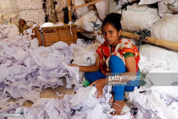 workers sorting through garment leftovers (waste) at a jhoot godown - fábrica têxtil imagens e fotografias de stock