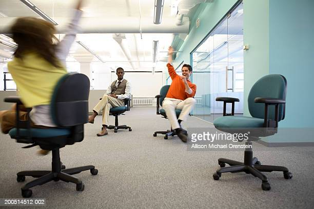 Workers spinning in chairs in office