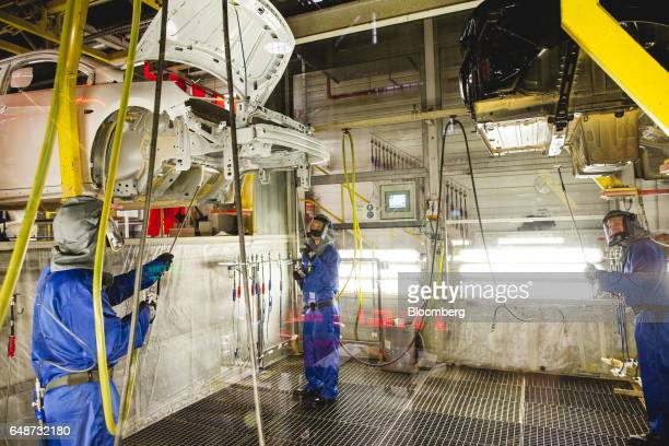 Workers spray a wax coating to the underside of an Opel Astra automobile body shell at the Opel automobile plant in Gliwice Poland on Monday March 6...