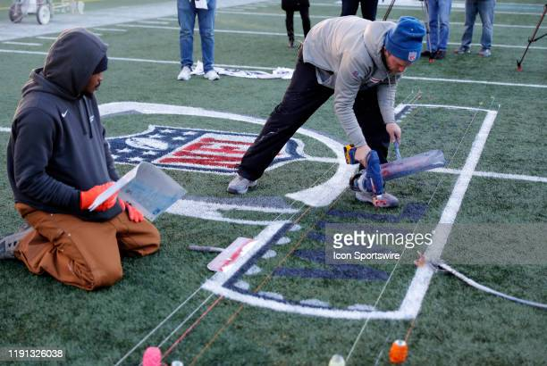 Workers spray paint the NFL Wild Card logo onto the field during press conferences in advance of the AFC Wild Card Game between the New England...