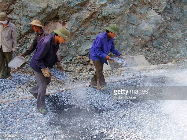 Workers spraying gravel over hot asphalt at a road construction site, in a remote mountainous region in the North of Vietnam. In some undeveloped...