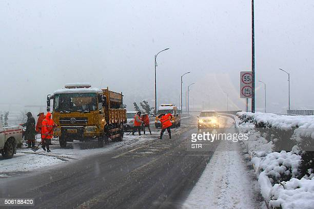Workers spread salt over a snowcovered highway in Tonglu county in Hangzhou east China's Zhejiang province on January 22 2016 Schools have been...