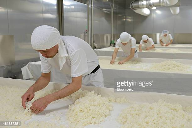 Workers spread steamed rice on tables in a hot room where the rice is treated with a mold called 'koji' in preparation for brewing sake at the...