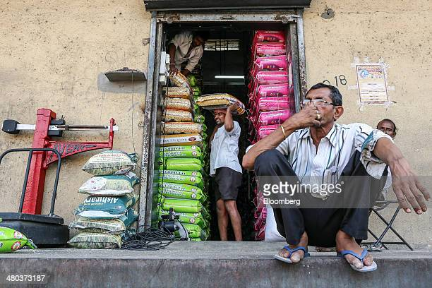 Workers stack bags of kolam rice at a warehouse in the Vashi Agricultural Produce Market Committee wholesale market in Mumbai India on Monday March...