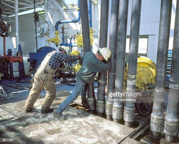 Workers stack pipe after pulling it from 8900 feet March 19 2001 in order to change a drill bit on a natural gas drilling rig in Lysite Wyoming The...