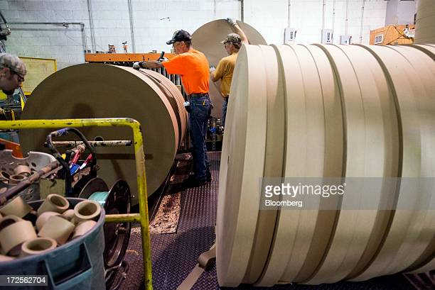 Workers stamp cut rolls of of paperboard before it's wrapped and prepared for shipping at Newark Recycled Paperboard Solutions in Baltimore Ohio US...
