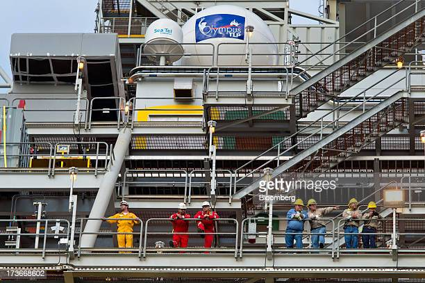 Workers stand aboard the Royal Dutch Shell Plc Olympus tension leg platform as it sets sail from Kiewit Offshore Services in Ingleside Texas US on...