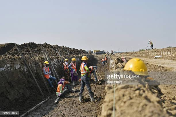 Workers stand and sit in a trench at an under construction sewerage system on the project site for a 920squarekilometer industrial area located on...