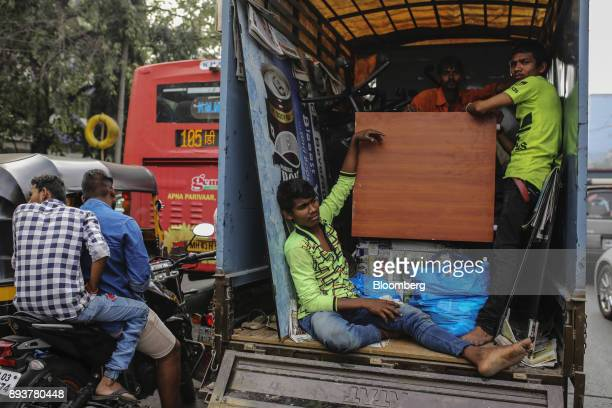 Workers stand and sit inside a truck as they transport goods in Mumbai India on Friday Dec 15 2017 India's inflation surged past the central bank's...