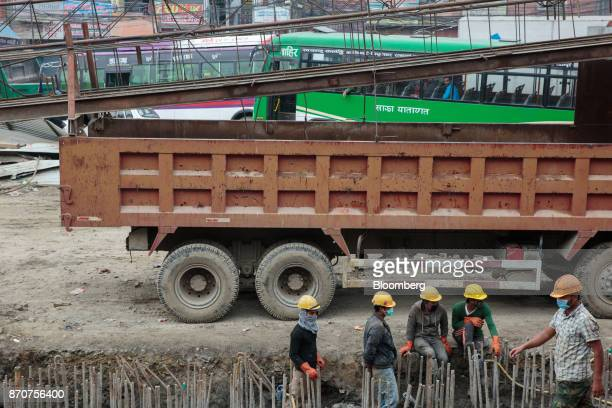 Workers stand at a construction site for a road operated by Shanghai Construction Group Co in the Kalanki Chowk area of Kathmandu Nepal on Wednesday...