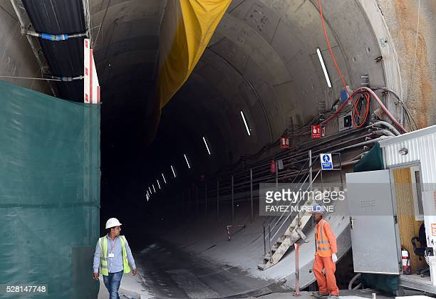 Workers stand at the entrance of a tunnel on May 4 2016 at a construction site of a section of the Saudi capital Riyadh's $225 billion metro system...