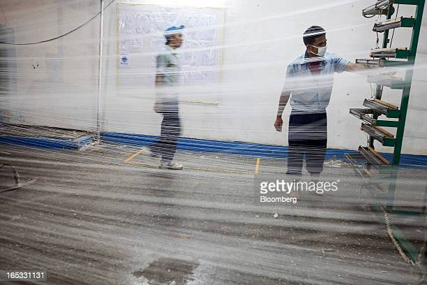 Workers stand behind lines of thread hanging from a yarn machine in the spinning area at a PT Sri Rejeki Isman factory in Sukoharjo Java Indonesia on...