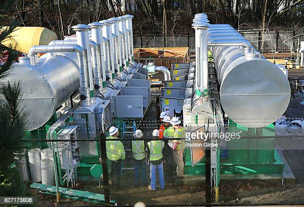 Workers stand between large tanks at the Spectra and National Grid gas pipeline control stations on Grove Street in the West Roxbury neighborhood of...