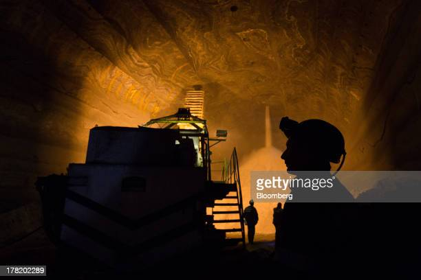 Workers stand by as excavated potash pours from the tunnel ceiling into an underground storage area at a potash mine operated by OAO Uralkali in...