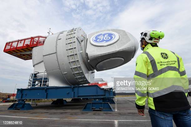 Workers stand by the first of 80 Haliade 150-6MW Offshore Wind Turbine produced for France's future first wind farm off Saint-Nazaire, at the General...
