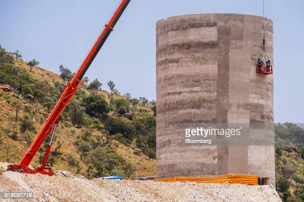 Workers stand in a cradle suspended from a crane during construction work on a raw ore stockpile storage silo at the Northam Platinum Ltd Booysendal...