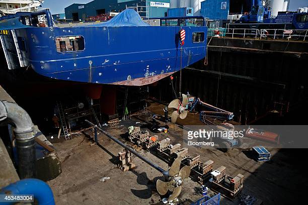 Workers stand in a dry dock as they maintain the propellers of the offshore supply ship Grampian Talisker operated by a North Star Shipping Ltd a...