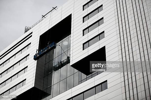 Workers stand in a suspended gantry as they clean the newly installed windows of No 5 Broadgate an office complex to be occupied by UBS AG as...