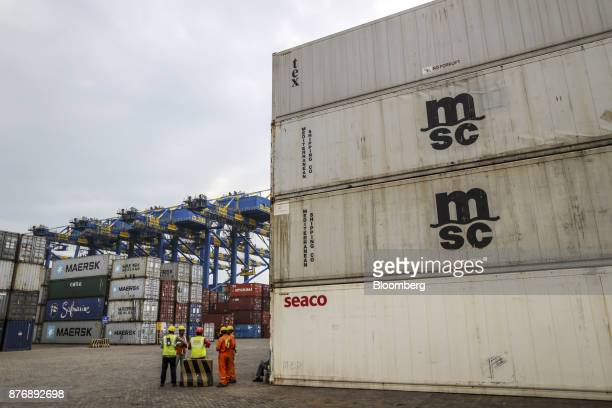 Workers stand in front of containers stacked in a yard at Krishnapatnam Port in Krishnapatnam Andhra Pradesh India on Monday Aug 11 2017 Growth in...