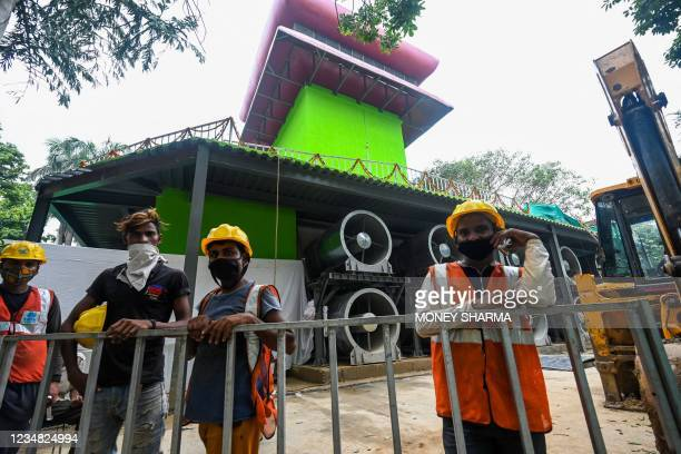 Workers stand in front of the 25-metre high smog tower, built to purify the air during pollution season, in New Delhi on August 23, 2021.