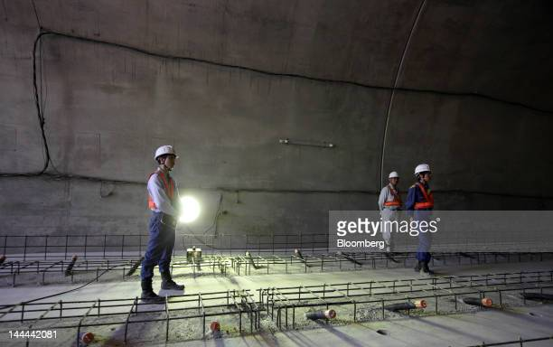 Workers stand in the Akiyama tunnel which is under construction for Central Japan Railway Co's magneticlevitation train line in Uenohara City...