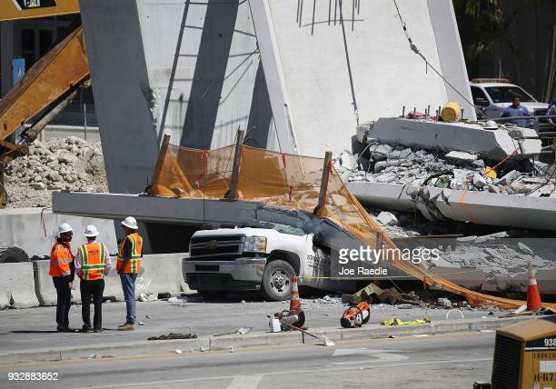 Workers stand near a crushed vehicle as law enforcement and members of the National Transportation Safety Board investigate the scene where a...