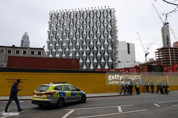 Workers stand near a police car outside the new US embassy building under construction in south London on June 7 after police carried out controlled...