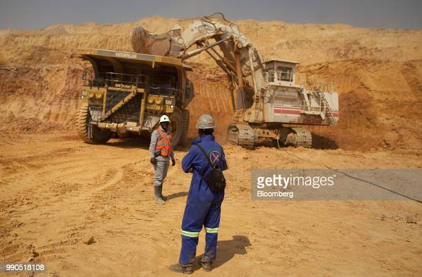 Workers stand near a Terex Corp mining excavator as it loads ore into a Caterpillar Inc truck during excavations at Katanga Mining Ltd's KOV copper...